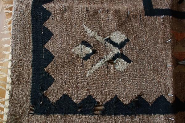 Uszkodzony fragment starego kilimu przed naprawą