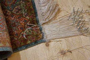 Frędzle dywanu jedwabnego w trakcie naprawy