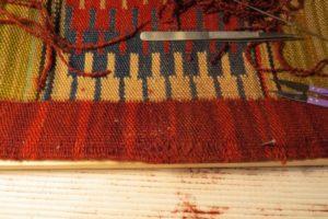 Rozerwany brzeg kilimu po naprawie