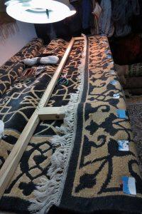 Brzeg dywanu nabity na ramę do renowacji frędzli