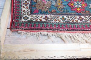Lewa strona dywanu z uszkodzonymi frędzlami